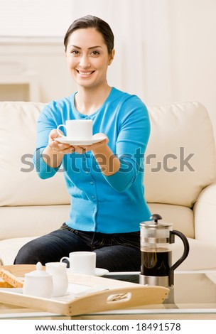 Hostess offering coffee to guest in livingroom - stock photo