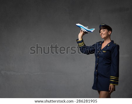 hostess plaing with a toy plane, dark background - stock photo
