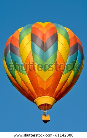 Hot Air Balloon against a blank blue sky - stock photo