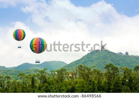 Hot air balloon flies over mountains with chinese temple - stock photo