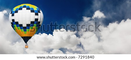 Hot air balloon flying in blue sky - stock photo