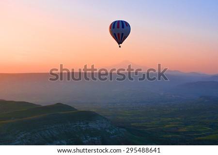 Hot air balloon flying over amazing landscape at sunrise, Cappadocia, Turkey  - stock photo