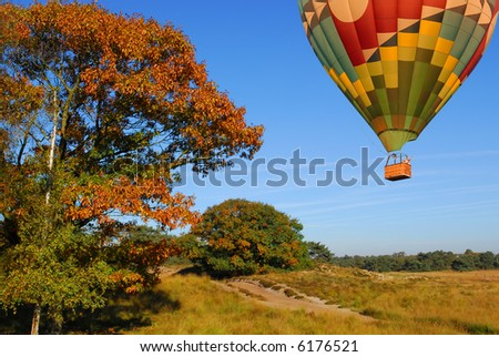 hot air balloon flying over autumn landscape - stock photo