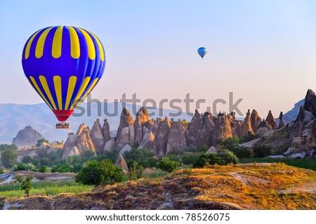 Hot air balloon flying over bizarre rock landscape in Cappadocia, Turkey - stock photo
