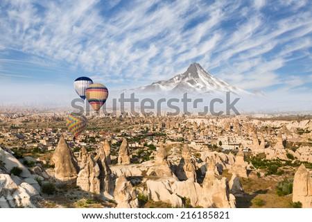 Hot air balloon flying over  Cappadocia, next to erciyes mountain - stock photo