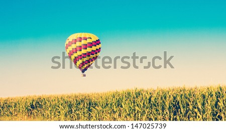 Hot air balloon flying over corn fields against blue sky in old style - stock photo