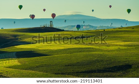 Hot air balloon flying over green field landscape at Cappadocia Turkey - stock photo
