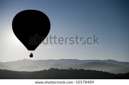 Hot air balloon flying over highest mountains in Spain. - stock photo