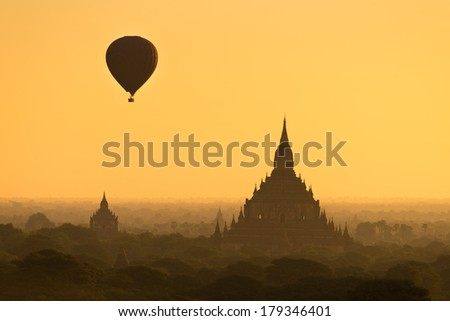Hot air balloon flying over old pagoda in Bagan - stock photo