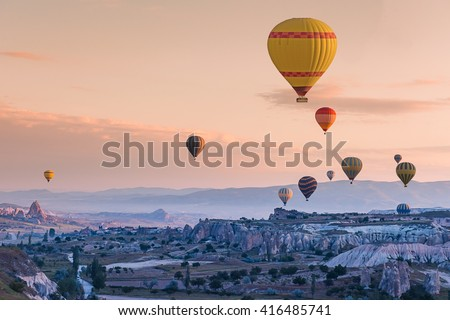 Hot air balloon flying over red poppies field Cappadocia region, Turkey - stock photo