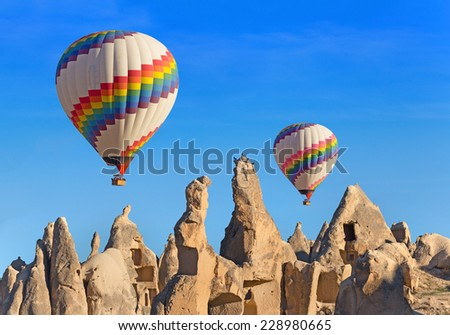 Hot air balloon flying over rock landscape at Cappadocia Turkey. - stock photo