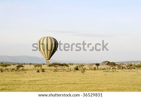 Hot air balloon flying over Serengeti National Park, Tanzania - stock photo