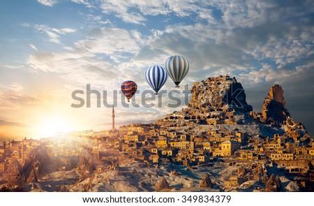 Hot air balloon flying over spectacular Cappadocia - stock photo