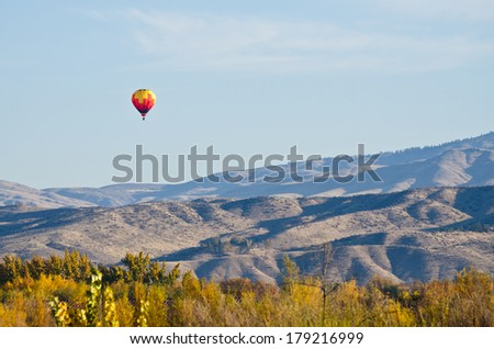 Hot Air Balloon Flying Over The Foothills - stock photo