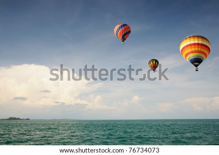 Hot air balloon flying over the sea - stock photo