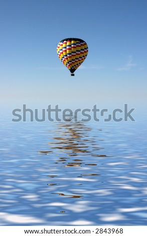 hot air balloon flying over water - stock photo