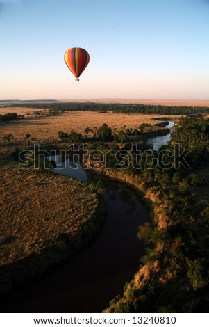 Hot Air Balloon hovers over the winding Mara River in the Masai Mara Reserve (Kenya) - stock photo