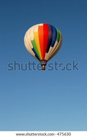 hot air balloon in flight, white balloon with rainbow colors against clear blue sky