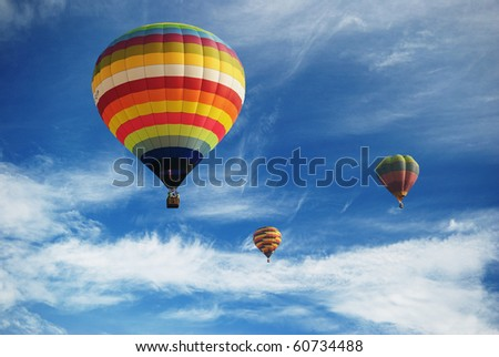 Hot air balloon in the cloudy blue sky - stock photo
