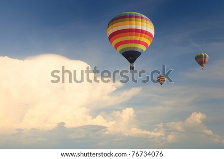 Hot air balloon in the cloudy blue sky during sunset - stock photo