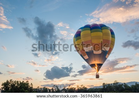 hot air balloon is flying at sunrise - stock photo