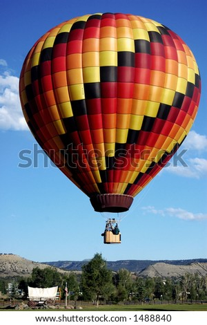 Hot Air Balloon lifting off for morning flight above covered wagon - stock photo
