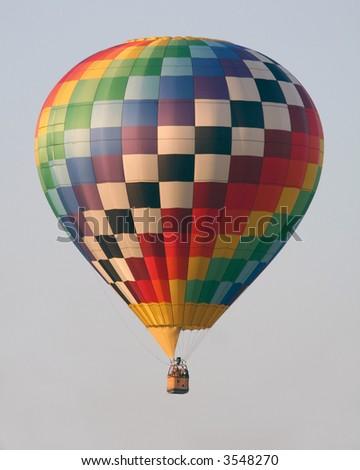 Hot air balloon moving across horizon - stock photo
