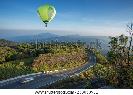 Hot air balloon over high mountain and road - stock photo
