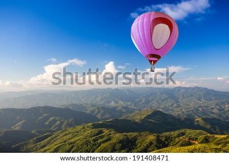 Hot air balloon over mountain - stock photo