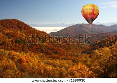 Hot Air Balloon Over Mountainous Autumn Landscape - stock photo
