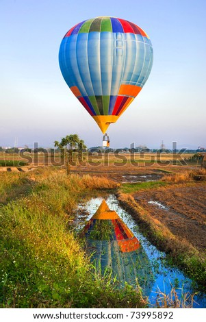 Hot air balloon Over paddy field reflecting in small river, ChiangMai , Thailand - stock photo