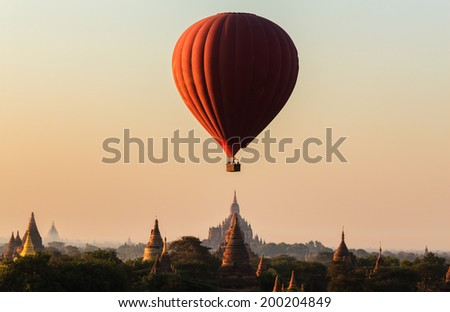 Hot air balloon over plain of Bagan in misty morning, Myanmar - stock photo