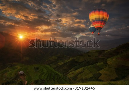 Hot air balloon over Rice fields on terraced in rainny season at Mu cang chai, Vietnam. Rice fields prepare for transplant at Northwest Vietnam