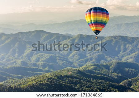 Hot air balloon over the mountain - stock photo