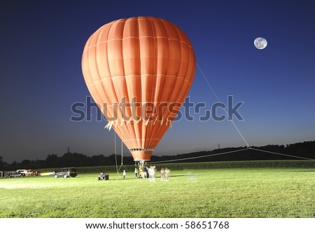 Hot air balloon ride after sunset on a full moon night - stock photo
