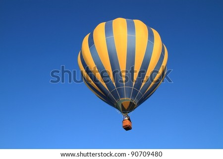 hot air balloon rises into pure, sunny blue sky at morning