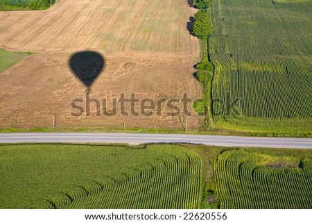 Hot air balloon shadow on field with road.