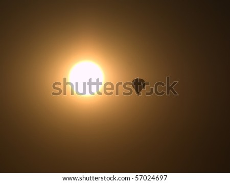 hot air balloon silhouette near the sun - stock photo