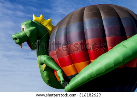 Hot air balloon with dragon shaped surrounding balloon on ground before take off - stock photo