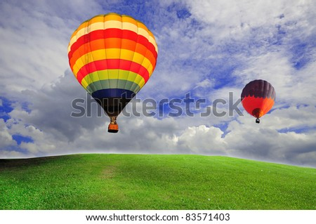 hot air balloon with green field and blue sky - stock photo