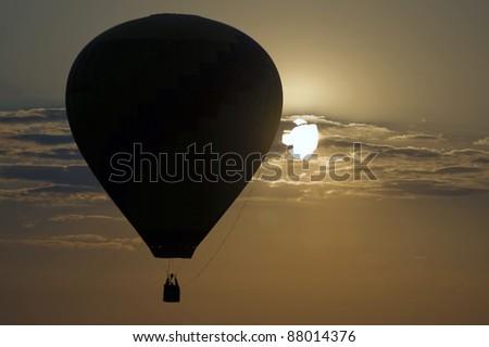 Hot air balloon with setting sun - stock photo