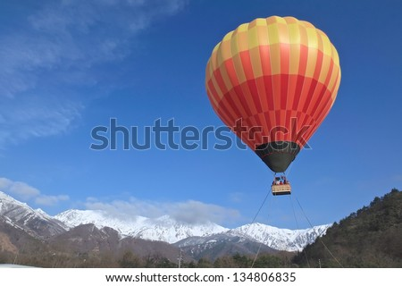 Hot air balloon with vivid colors - blue sky and snow background. - stock photo