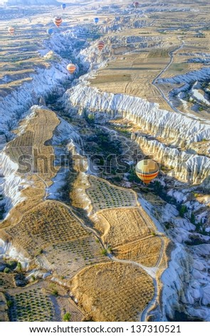 Hot air balloons above a gorgeous landscape of Cappadocia in Turkey - stock photo