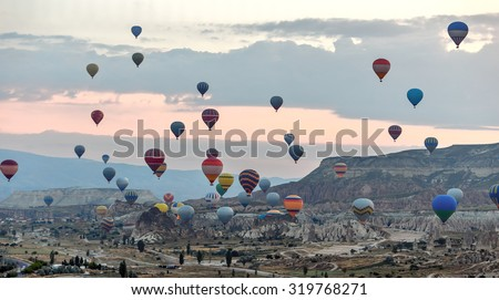 Hot air balloons (atmosphere ballons) flying over mountain landscape in the  Cappadocia at sunrise, UNESCO World Heritage Site since 1985) - Turkey - stock photo