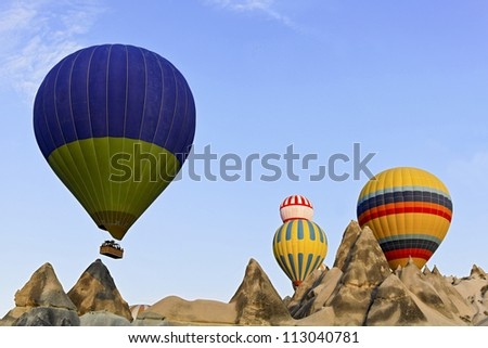 Hot air balloons captured coming over the limestone ridge in Caapadocia, Turkey. Weathered mineral peaks which have eroded through evolution present a backdrop to the striking colors of the balloons