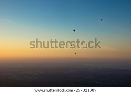 Hot air balloons float through the sky at sunrise - stock photo