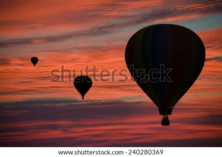 Hot-air balloons floating among pink and orange clouds at dawn - stock photo