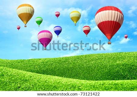 Hot air balloons floating over green field - stock photo