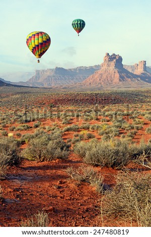 Hot air balloons floating over the southeastern desert of Utah in Valley of the Gods near the city of Bluff at sunrise. - stock photo