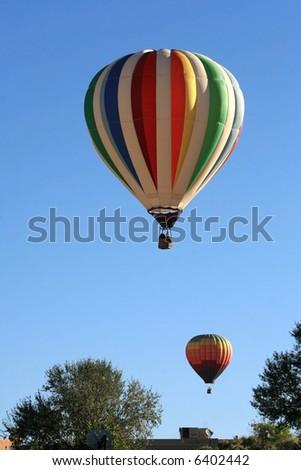Hot Air Balloons fly over a residential area during the 2007 Albuquerque Balloon Fiesta - stock photo